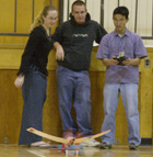 Shannon Cartmill and Cris Colflesh watch as Tuan Dinh attempts a takeoff with their radio controlled model airplane during testing in the Darlene May Gym for Dr. Don Edberg's Aero 101 class.
