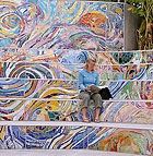 Lora Hall, a masters student in regenerative studies, sits in the Lyle Center for Regenerative Studies amphitheater amid a mosaic mural done by university art students.
