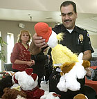 Corporal T.J. Garcia of the Pomona Police Department and Alice Mattingly look over donated stuffed animals during the Staff Council Holiday reception in the CLA building.