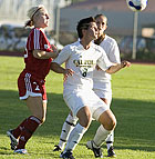 Lindsey Zuber and Linsey Latham converge on the ball during season opener against Biola University at Cal Poly Pomona.