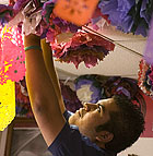 Luis Martinez, a junior computer engineer, hangs paper flowers from the cieling in preparation for Dia De Los Muertos at the Cesar Chavez Center at Cal Poly Pomona.