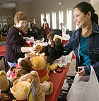 Maria Duenas and Alice Mattingly add stuffed animals to a pile that will be given to the Pomona Police Department for distribution during Holiday Gathering sponsored  by the Cal Poly Pomona Staff Council.