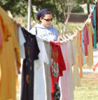 Patty Moncada looks over shirts on display at Cal Poly Pomona as part of the Clothesline Project, which provides an opportunity for the community to bear witness through hand made shirts to  personal experiences of violence.