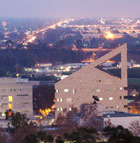 Cal Poly Pomona's CLA building is framed by the lights of the city as dusk falls.