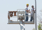 Khin Phong Ung and Reuben Lopez install a light pole on Eucalyptus Lane at Cal Poly Pomona.