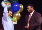 Julio Fonseca from Los Olivos Dining Services   carries balloons with him as he receives his 10 years of service pin from Ray Inge during the 2002 Service Awards at the Univesity Theatre at Cal Poly Pomona during Fall  Conference.