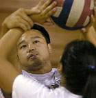 Assistant coach Vinh Nguyen works with players on setting mechanics during volleyball camp at Cal Poly Pomona