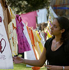 Jodie Wims, a third year public relations major, looks at decorated shirts that are part of The Clothesline Project,  a testimonial from survivors of assault, rape and incest.