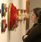 Karla Hernandez looks at masks, part of the Visual Voices Against Violence art exhibit meant to bring awareness to the plight of domestic violence and sexual assault victims at the Kellogg Art Gallery.