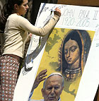 Gloria Reyes, a third year Psychology major, signs a memorial tribute for the late Pope John Paul II following a memorial mass.