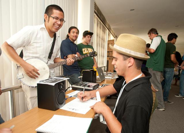 Jason Ebueng, a senior music major, talks with Jorge Preciado about music clubs during the Orientation Club Fair July 6, 2011.