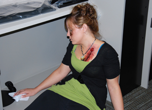 Kelly Walter, who is a student as well as community service officer on campus, plays the role of a shooting victim, with moulage makeup depicting a chest wound.