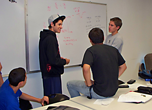 QUEST students work out a problem on the whiteboard during the 2011 summer program.