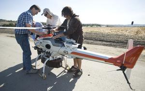 Sophomore Hovig Yaralin, Don Edberg, Subodh Bhandari and Jim Cesari prepare the UAV helicopter for its first flight.