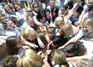 The women of Chi Omega huddle and cheer during the 2004 Greek Week carnival.