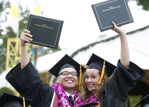 College of Science graduates of 2009 hold up their diplomas.