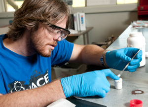 Chemical engineering senior Jordan Koch prepares a pack, which is a blend of powders and a metallic sample in a ceramic crucible.