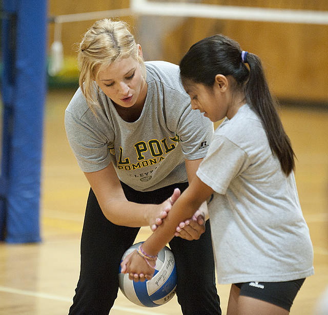 Ashley Marshman,  an outside hitter on the Cal Poly Pomona volleyball team, works with Rena Rodriguez, 12,  on her digging form during volleyball camp at Cal Poly Pomona.