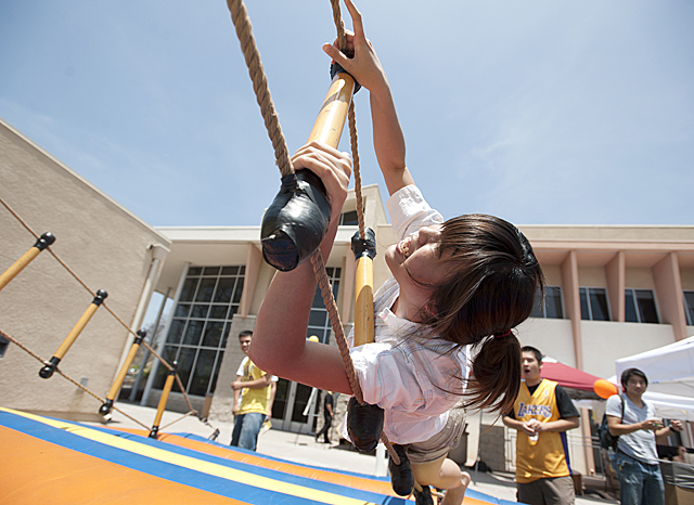 Wynnie Au, a HRT freshman,  begins to tumble off a balance game during an end of year carnival at the Collins College of Hospitality Management .