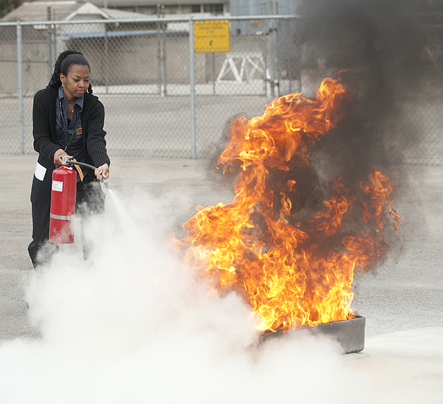 Trinette Briggs, a career counselor at the Career Center, puts out a blaze during fire extinguisher training at Cal Poly Pomona.