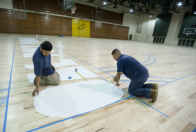 Workers position  letters along the baseline of  Kellogg Gymnasium as they prepare to stripe the gym floor.