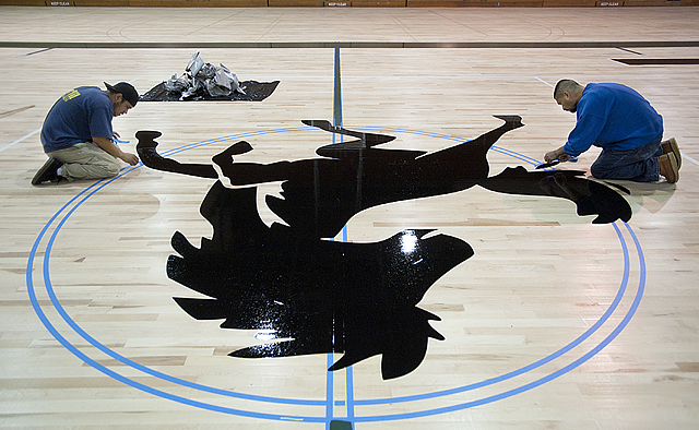 Jesus Gonzalez and Mario Morales attend to details on the Bronco at center court  on the new floor at  Kellogg Gym.