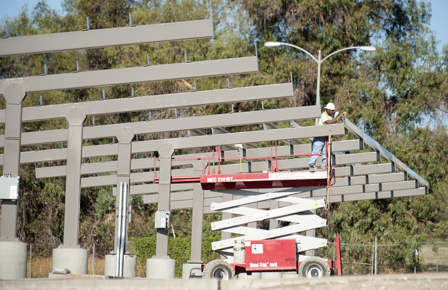 A worker prepares supports that will hold solar panels at Parking Lot M at Cal Poly Pomona.
