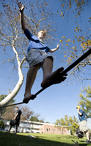 John Sorlie crosses a slackline in the Cal Poly Pomona quad.