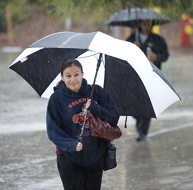 Jessica Sanchez uses a big umbrella during a rainstorm at Cal Poly Pomona.