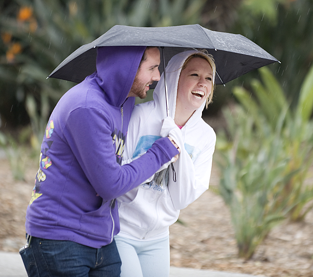 A pair of students share an umbrella as rain falls at Cal Poly Pomona.