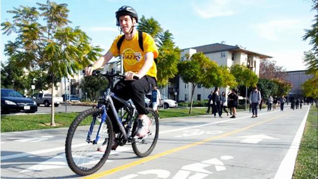 A bicyclist uses the new bike path from Lot B to the Bronco Student Center.