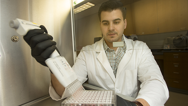 Jonathan Tringali, a biology graduate student and a participant in the BioTiER program, works in the BioScience Building.