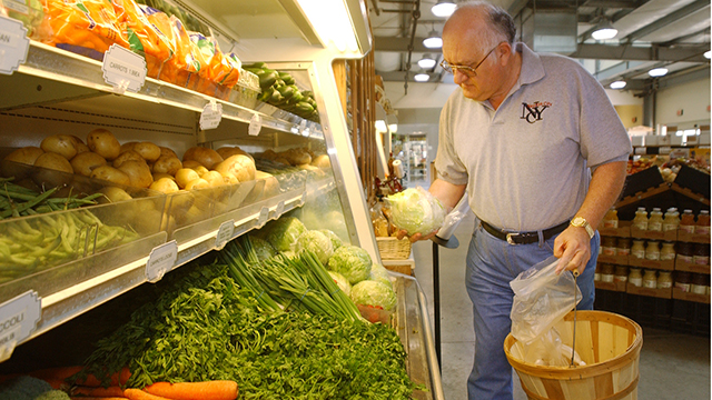 A shopper looks at produce in the Farm Store.