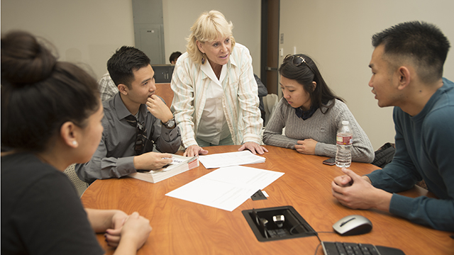 An instructor works with Asian American students in the College of Business Administration.