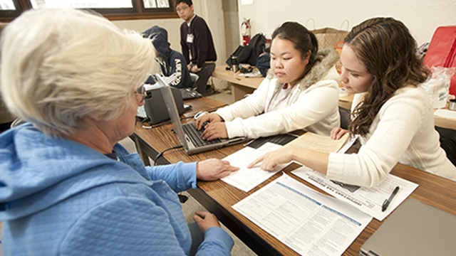 Accounting students helping a woman with income tax preparation.