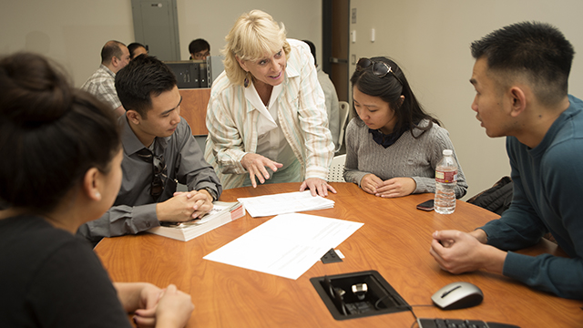 Professor Rhonda Rhodes works with students in her class at the College of Business Administration.