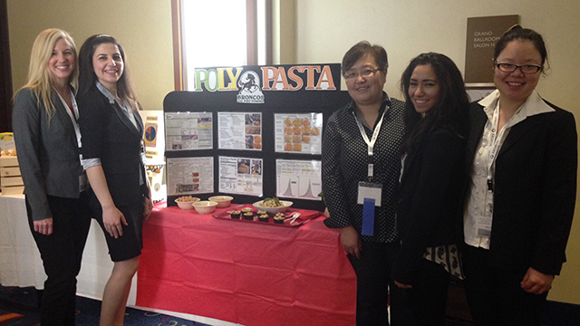 "Food science and technology students with their adviser, Professor Olive Li, standing in front of their display for ""Poly Pasta."""