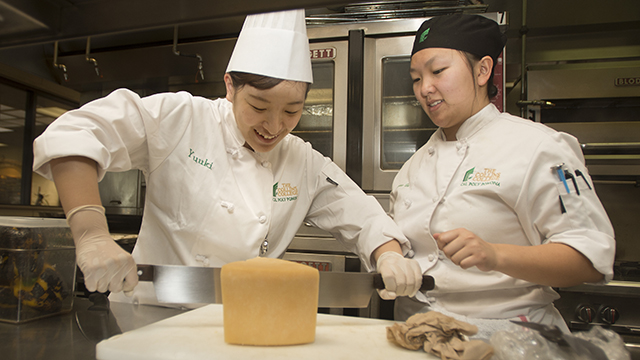 Collins College student Cecilia Ho, right, shows a student from Toyo University in Japan how to cut a Parmesan cheese in the kitchen at the Restaurant at Kellogg Ranch.