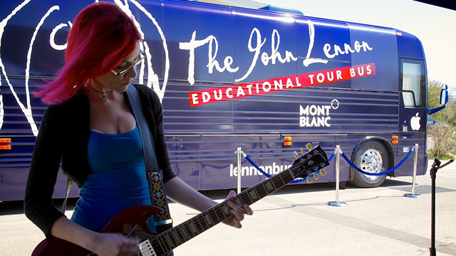 An electrical guitarist plays in front of the John Lennon Tour Bus.
