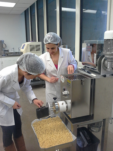 """Students use a pasta extruder in the food technology lab to create """"Poly Pasta."""""""