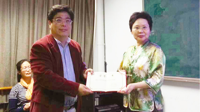 Professor Lianlian Lin (right), receives an honorary certificate for giving a presentation in Beijing.