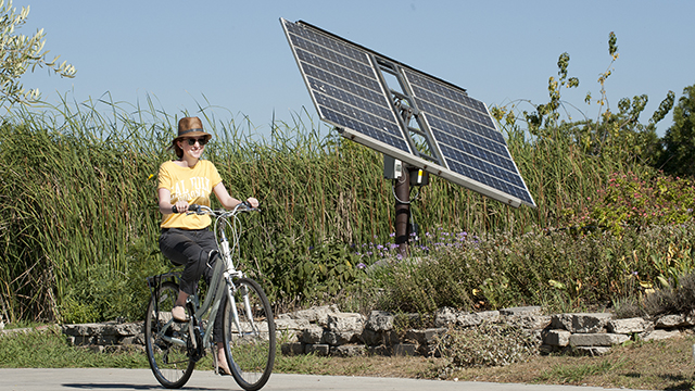 A student rides her bicycle by a photovoltaic panel at the Lyle Center for Regenerative Studies.