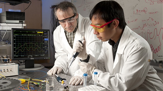 Professor Ertan Salik works with a student in the Photonics Research lab.