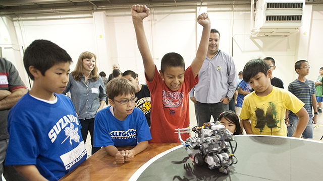 Students celebrate a win during the Sumo Challege at the 2013 Robot Expo at the Fairplex.