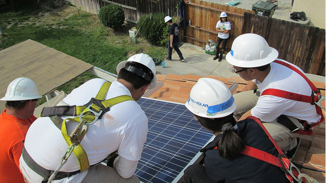 Cal Poly Pomona engineering students work on installing solar panels on a home in San Bernardino County.