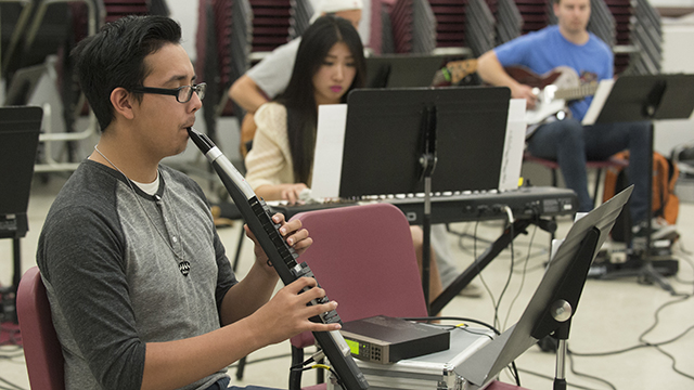 Jose Moreno plays at EWI or electric wind instrument during a MIDI Ensemble rehearsal.