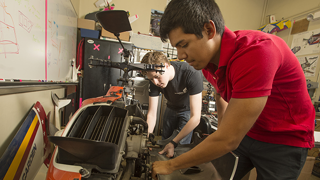 Ramon Navarro and Michael Rose work on a R-Max helicopter in the aerospace lab at Cal Poly Pomona.