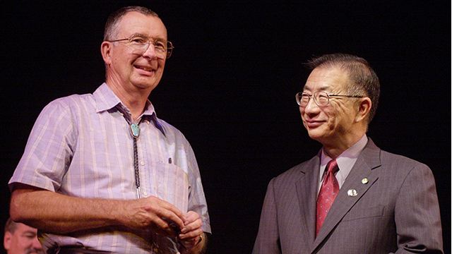 Biology Professor Martin Stoner receives his 35-year pin from then-President Bob Suzuki, right, during the 2002 Service Awards.