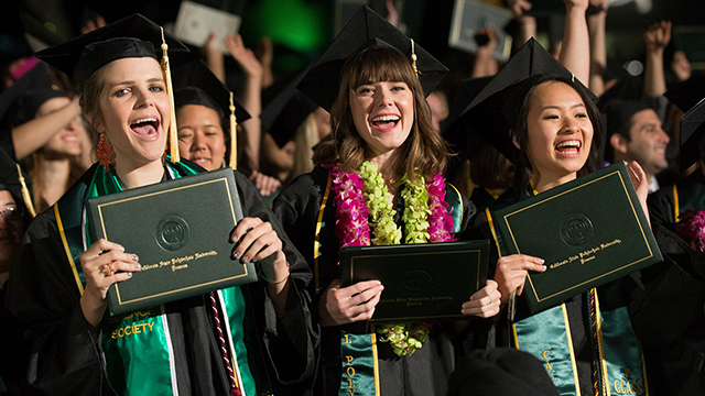 A trio of new graduates are all smiles as they clutch their diplomas and celebrate at the College of Agriculture's commencement ceremony on June 13, 2014.