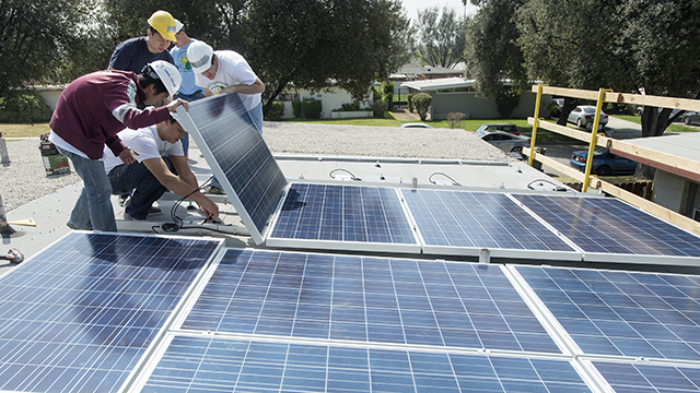 Cal Poly Pomona engineering technology students install 16 solar panels on a home in Redlands as part of Alternative Spring Break in 2013, similar to the environmental sustainability efforts that the university plans to increase.